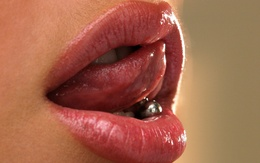 Piercing the language of the wallpaper in a woman's mouth lips