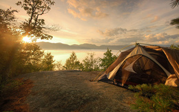 Wallpaper tent with a view of the sunset over the lake water